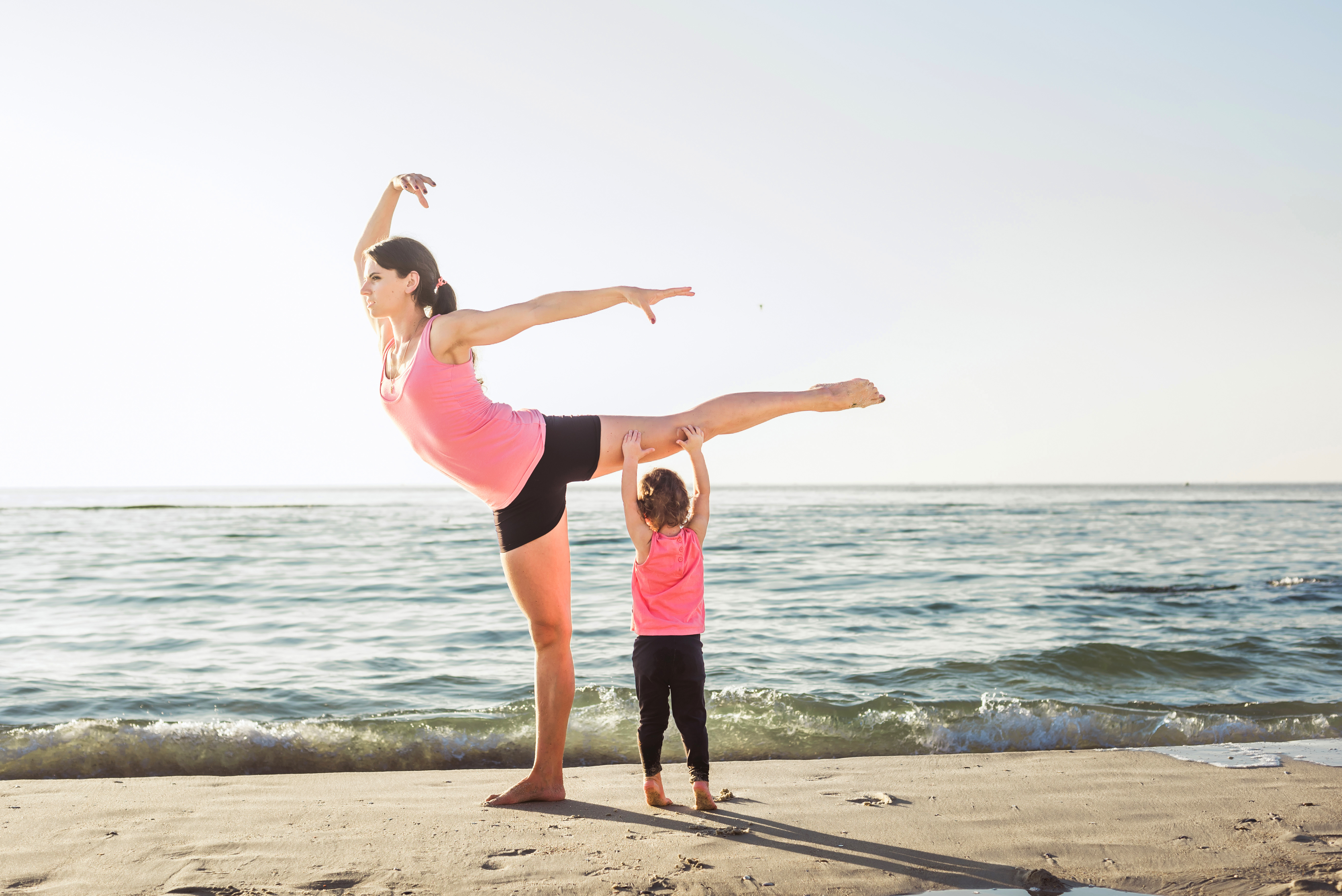 Woman Completing Yoga Exercise While Watching Children